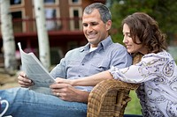 Middle-aged couple reading the newspaper together outdoors (thumbnail)