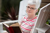 Middle-aged woman reading book in adirondack chair (thumbnail)