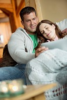 Mid-adult couple cuddled on sofa with pc tablet (thumbnail)