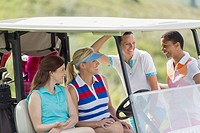Female golfers having a laugh by golf cart