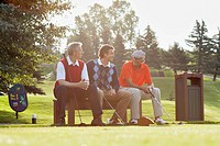Three golfers sitting on bench by tee_box