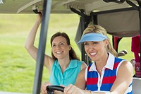Pretty, female golfers driving in golf cart