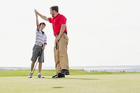 Father and pre_teen son giving a high_five while golfing