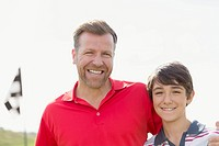 Portrait of father and pre_teen son on golf course