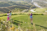 Female golfer driving golf ball while golfing friends watch