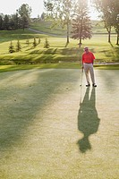 Senior male golfer standing on green creating long shadow