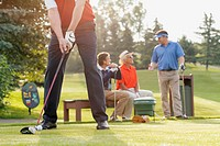 Middle_aged golfer ready to drive golf ball off tee_box