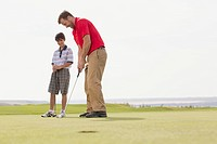 Pre_teen boy watching father make golf putt