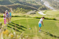 Middle_aged female golfer teeing off while friends watch