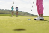 Close_up of golf ball and putter with female golfers in background