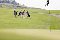 Foursome of female golfers walking on fairway