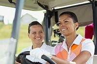 Middle_aged female golfers smiling in golf cart