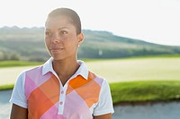 Pretty, African American female golfer gazing off on golf course.