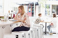 Woman sitting and bar counter and using laptop