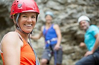 Portrait of female rock climber with 2 climbers behind her