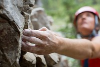 Focus on hand of middle_aged female rock climber.