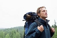 Male backpacker breathing in fresh air with eyes closed