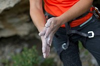Close_up of female rock climber rubbing chalk on hands