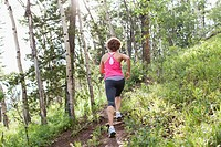 View from behind of female runner in the woods