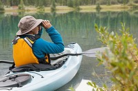 Woman looking through binoculars while sitting in kayak