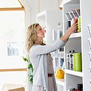 Portrait of sales clerk putting products on shelf