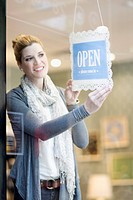 Smiling woman putting up open sign