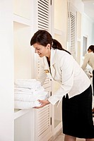Chambermaid with fresh towels in hotel room