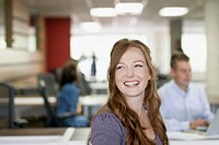 Pretty redhead office worker smiling at the office (thumbnail)