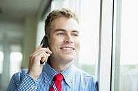 Handsome, young adult male office worker on smartphone