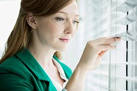 Female office worker looking through window blinds
