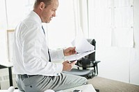 Middle_aged businessman reviewing report in office