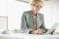 MIddle_aged businesswoman using pc tablet in modern office.
