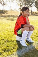 Girl soccer player sitting on soccerball on sidelines