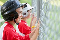 Two young male baseball players watching game from behind chainlink fence