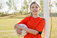 Smiling nine year old female soccer player with soccerball