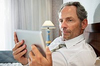 Man using tablet pc in bedroom