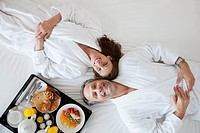 Couple lying on bed with breakfast on side