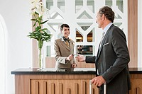 Female receptionist in hotel reception giving keys to man