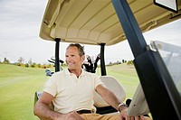 Man sitting in golf cart on golf course