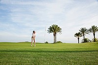 Woman playing golf on golf course