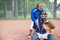 Coach standing behind young male baseball catcher