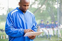 Baseball coach using pc tablet at ball game