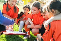 Girls soccer team looking at playbook with coach (thumbnail)