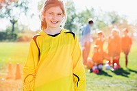 Portrait of young female soccer player with team in background (thumbnail)