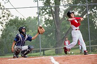 Young male baseball player swinging at baseball