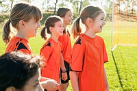 Girl soccer players standing on field together (thumbnail)
