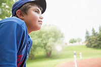 Twelve year old baseball player watching game from bench