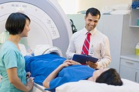 Doctor and technician having conversation with patient on MRI table
