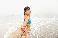 Woman pulling man by hand on beach (thumbnail)