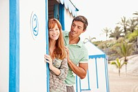 Smiling couple standing near beach hut